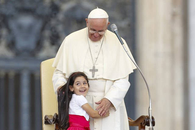 A young girl smiles as she embraces Pope Francis during an audience in St. Peter's Square at the Vatican June 14 for families participating in the pastoral conference of the Diocese of Rome. (CNS/Reuters)