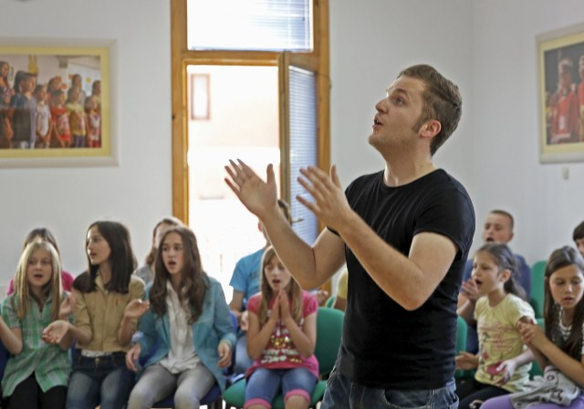 """Ismar Poric, choirmaster of children's choir """"Superar,"""" and choir members practice the songs they will perform for Pope Francis' visit to Sarajevo, Bosnia-Herzegovina, at their music school in Srebrenica. Pope Francis will make a one-day trip to Sarajevo June 6. (CNS/Reuters)"""