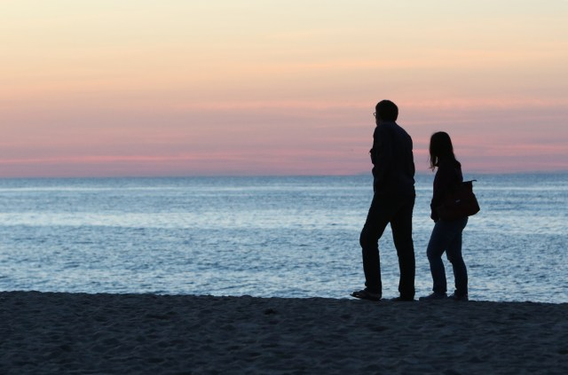 A man and woman walk near the Atlantic Ocean on Race Point Beach in Provincetown, Mass., June 3. The Vatican has announced that Pope Francis' encyclical on the environment,