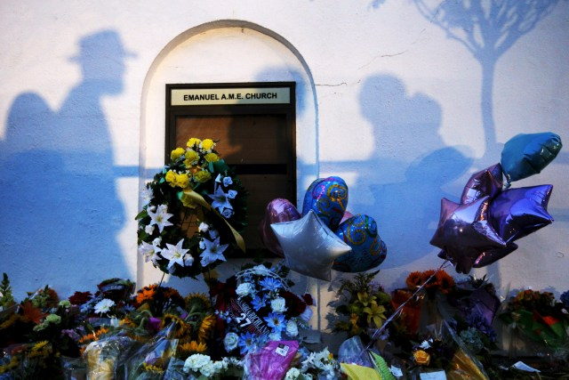 Mourners cast shadows on the wall of a makeshift memorial at the Emanuel African Methodist Episcopal Church in Charleston, S.C. June 18. Nine people were murdered the day before during a Bible study session at the church. (CNS/Reuters)