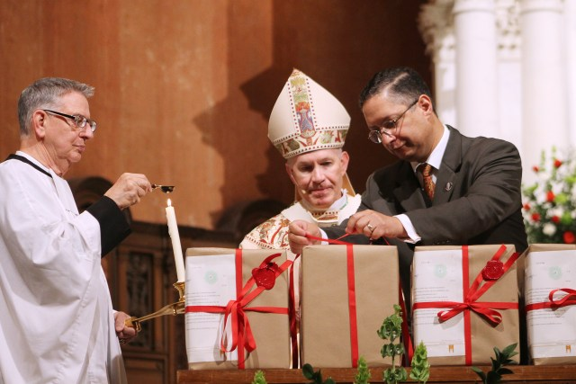 Archbishop George J. Lucas of Omaha, Neb., watches Omar Gutierrez as he ties a ribbon on one of the boxes of documents detailing the archdiocese's investigation for the sainthood cause of Irish-born Father Edward Flanagan, who founded Boys Town in Nebraska. (CNS/Susan Szalewski, Catholic Voice)