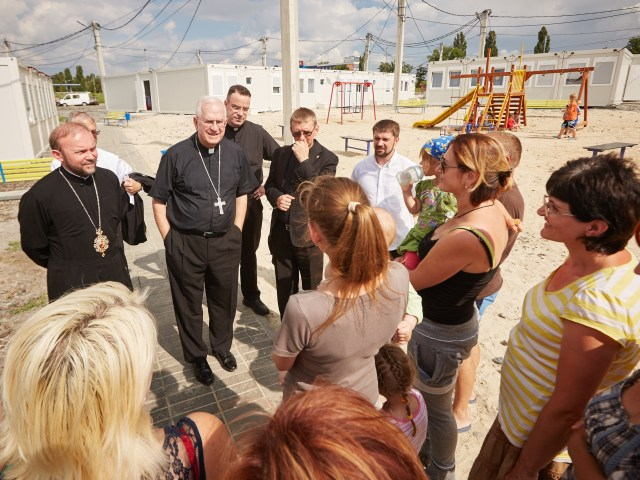 Archbishop Joseph E. Kurtz of Louisville, Ky., center, president of the U.S. Conference of Catholic Bishops, and other church officials speak to internally displaced Ukrainians at a modular camp in Kharkiv, Ukraine, June 21. (CNS/EPA)