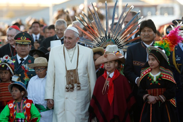 Pope Francis walks with Bolivian President Evo Morales and a group of children in traditional dress as he arrives in La Paz July 8. (CNS/Paul Haring)