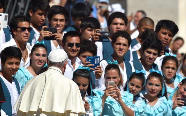 Dancers from Argentina take pictures of Pope Francis after his weekly audience in St. Peter's Square Aug. 26. (CNS/EPA)