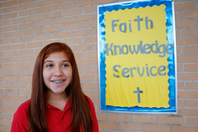 A student poses by an inspirational motto at St. Jerome School in Phoenix, Ariz. (CNS/Nancy Wiechec)