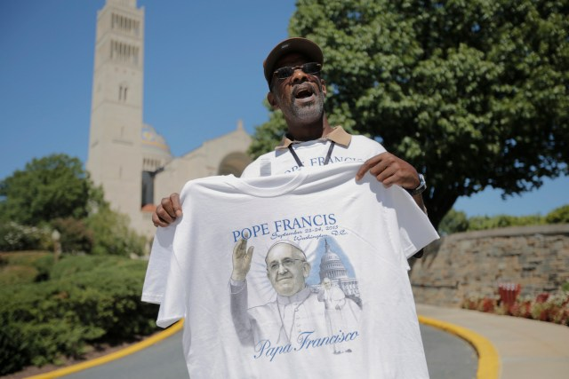 A man sells T-shirts with Pope Francis' picture Sept. 14 outside the Basilica of the National Shrine of the Immaculate Conception in Washington where Pope Francis will celebrate Mass Sept. 23. (CNS/Bob Roller)