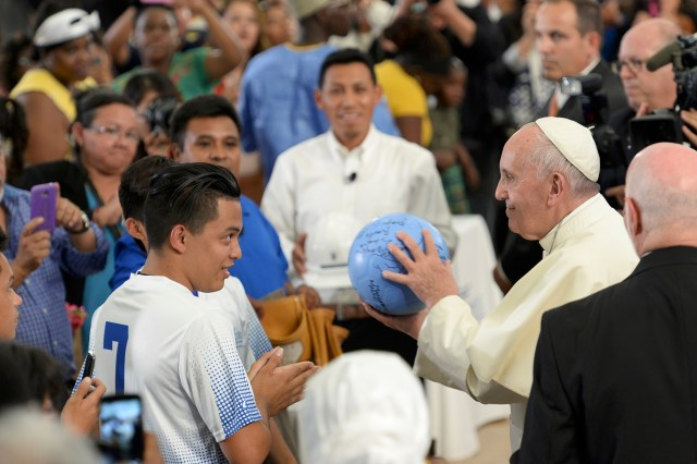 Pope Francis accepts an autographed soccer ball from the student team at Our Lady Queen of Angels School in the East Harlem area of New York Sept. 25. (CNS/Debbie Egan-Chin, pool)