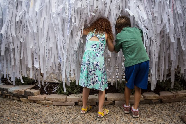 Leah Pepsin, 6, and Lucas Daniel, 6, both from Philadelphia, look through prayer ribbons at the Knotted Grotto outside the Cathedral Basilica of SS. Peter and Paul during the World Meeting of Families Sept. 25 in Philadelphia. Thousands of visitors added their prayer intentions to the project that was inspired by the image of Mary Undoer of Knots. (CNS/Joshua Roberts)
