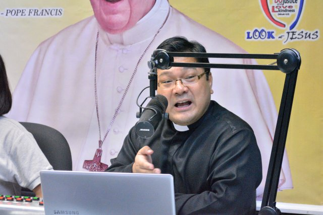 "Dominican Father Winston Cabading hosts the radio program ""Light in the Darkness"" Oct. 24, at Radio Veritas in Quezon City, Philippines. (CNS/Simone Orendain)"