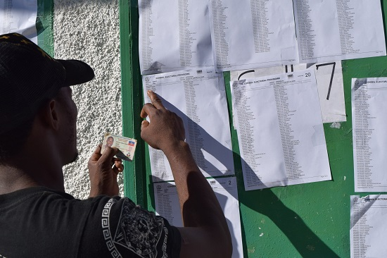 A man checks his voting location in Port Au Prince, Haiti's Aug. 9. Haiti's bishops urged people to vote Oct. 25, but warned them to beware of false promises and demagoguery. (CNS photo/Jean Jacques Augustin, EPA)