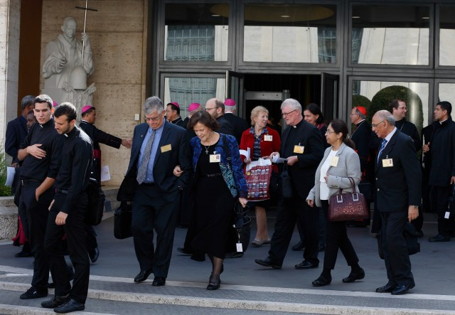 U.S. couple Anthony and Catherine Witczak, center, and other delegates leave a session of the Synod of Bishops on the family at the Vatican Oct. 15. The couple are observers at the synod. (CNS photo/Paul Haring)