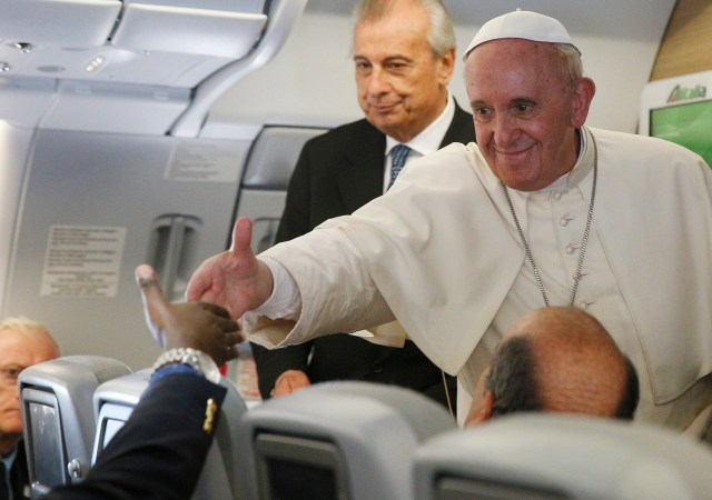 Pope Francis greets a journalist aboard his flight from Bangui, Central African Republic, to Rome Nov. 30. The pope answered questions from journalists for about an hour. (CNS/Paul Haring)