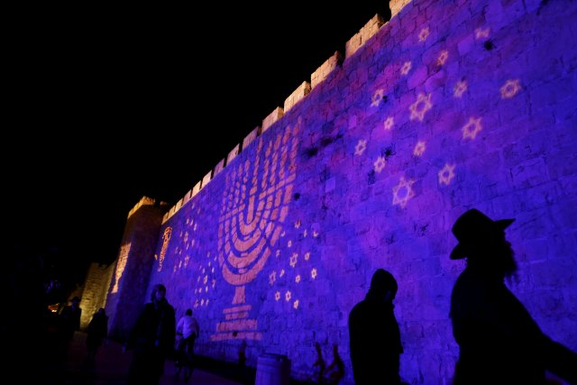 """People walk past an image of a Menorah projected on a wall surrounding the Old City of Jerusalem Dec. 8. Although Catholic are called to witness to their faith, the church """"neither conducts nor supports"""" any institutional missionary initiative directed toward Jews, according to a new document from a Vatican commission. (CNS photo/Ammar Awad, Reuters)"""