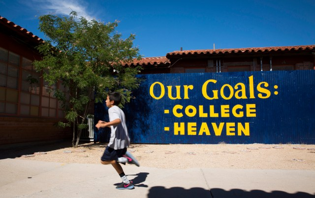 A fence is emblazoned with a Notre Dame ACE Academy slogan at St. Ambrose Catholic School in Tucson, Ariz. The expression reminds teachers and students that the school's main objective is to put children on the path to college and heaven. (CNS/Nancy Wiechec)