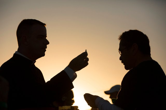 Msgr. J. Brian Bransfield gives Communion to a man attending Mass on the U.S. side of the border in El Paso, Texas, Feb. 17. About 550 guests situated on a levee north of the Rio Grande participated in the Mass Pope Francis celebrated in Ciudad Juarez, Mexico. (CNS/Nancy Wiechec)