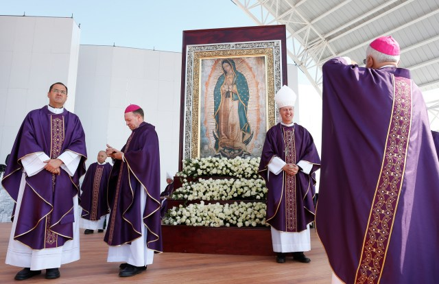 A bishop takes a photo of another bishop near an image of Our Lady of Guadalupe as they wait for Pope Francis' arrival to celebrate Mass in Ecatepec near Mexico City Feb. 14. (CNS/Paul Haring)