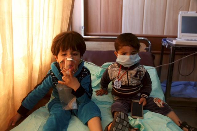 "Children receive oxygen at a hospital in Taza, Iraq, March 9, after Islamic State militants fired mortar shells and rockets filled with ""poisonous substances"" into their village. (CNS/Reuters)"