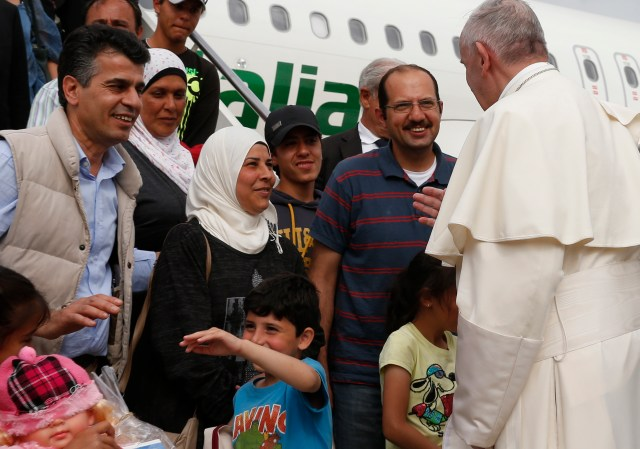 Pope Francis greets Syrian refugees he brought from Greece at Ciampino airport in Rome April 16. The pope concluded his one-day visit to Greece by bringing 12 Syrian refugees to Italy aboard his flight. (CNS/Paul Haring)