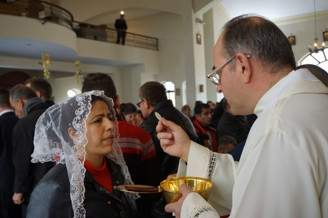 A priest gives Communion to a woman during a Mass for Iraqi Christian refugees at Our Lady of Peace Center on the outskirts of the Jordanian capital, Amman. (CNS/Dale Gavlak)