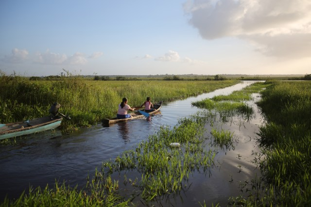 A woman and child paddle a boat in a marsh in 2015 along the Pomeroon River in the interior of Guyana. (CNS/Bob Roller)