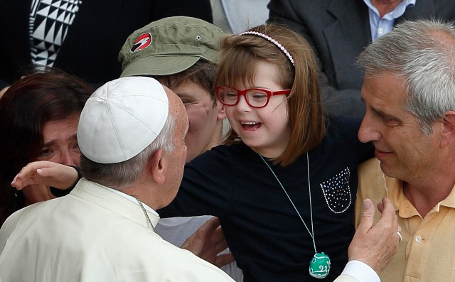 Pope Francis greets a girl after celebrating a Mass for the sick and disabled in St. Peter's Square at the Vatican June 12. The Mass was an event of the Jubilee of Mercy. (CNS/Paul Haring)