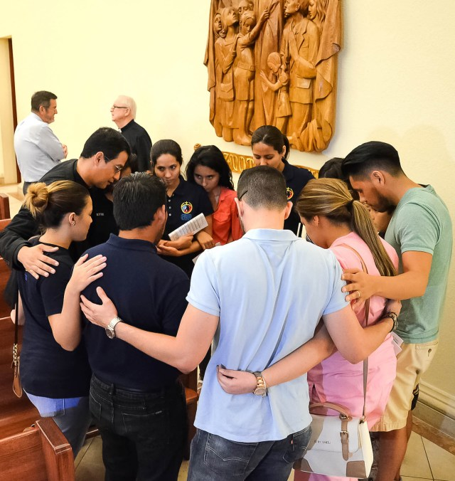 """Father Jorge Torres, director of vocations for the Diocese of Orlando, Fla., prays with young people who participated in the """"Vigil to Dry Tears"""" June 13 at St. James Cathedral in Orlando. Father Torres is among the Orlando diocesan priests lending a hand in counseling families and friends of victims of the June 12 massacre at Pulse nightclub in Orlando. (CNS/Andrea Navarro, Florida Catholic)"""