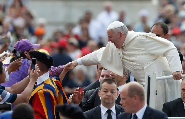 Pope Francis reacts as someone in the crowd holds onto his hand during his general audience in St. Peter's Square at the Vatican June 15. (CNS/Paul Haring)