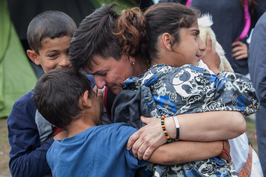 A volunteer from a humanitarian organization hugs refugee children June 13 during a police operation at a makeshift camp in Polykastro, Greece. (CNS/pool via EPA)