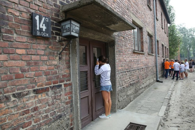 A World Youth Day pilgrim looks inside a building during a July 25 visit to the Auschwitz Nazi concentration camp in Oswiecim, Poland. (CNS/Bob Roller)