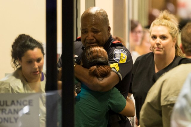 A Dallas police officer is comforted July 7 at Baylor University Hospital's emergency room entrance after a shooting attack. (CNS photo/Ting Shen, The Dallas Morning News handout via Reuters)
