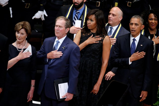 Former first lady Laura Bush, former U.S. President George W. Bush, first lady Michelle Obama and President Barack Obama hold their hands on their hearts as they sing the national anthem July 12 at a memorial service held in honor of police officers killed and wounded in shootings in Dallas. (CNS photo/Carlo Allegri, Reuters)