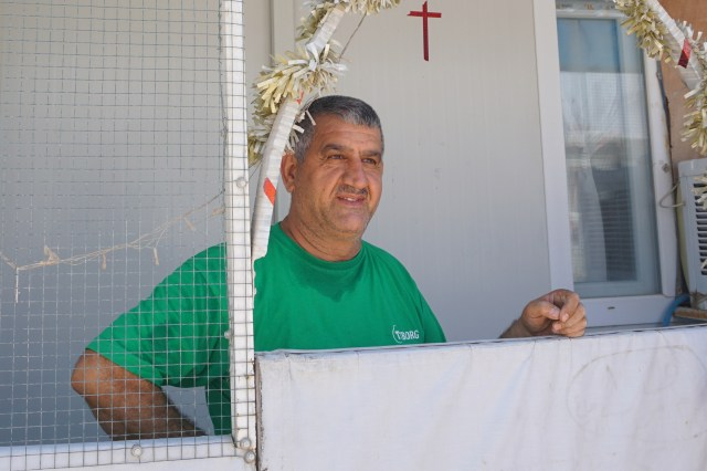 An Iraqi Christian spruces up his shelter July 24 with a cross and other Christian symbols at the the Ashti camp for internally displaced Iraqis in Ainkawa. Some 7,000 Christians, mainly Catholics, were forced to escape the Islamic State assault on Mosul and their surrounding villages two years ago and fled to Ainkawa, a Christian enclave of the Kurdish capital, Irbil. (CNS/Dale Gavlak)
