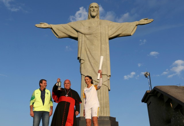 Cardinal Orani Tempesta of Rio de Janeiro holds the Olympic flame Aug. 5 as Rio Mayor Eduardo Paes and former Brazilian volleyball player Isabel Barroso look on in front of the Christ the Redeemer statue. (CNS/Reuters)