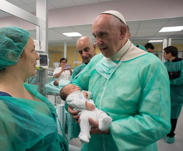 Pope Francis holds a baby as he visits the neonatal unit at San Giovanni Hospital in Rome Sept. 16. The visit was part of the pope's series of Friday works of mercy during the Holy Year. (CNS/L'Osservatore Romano)