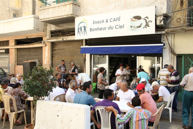 People dine outside at the Joy of Heaven, a free restaurant for the poor and needy in a suburb of Beirut. The restaurant serves about 200 people a day. (CNS/Johnny Antoun)