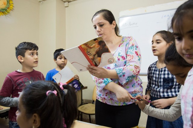 Basima Kamil, 42, a refugee from Iraq, teaches English Oct. 3 at the Don Bosco Youth Center in Istanbul. The children at this center are refugees mostly from Syria and Iraq. Kamil has been in Turkey since December 2012, waiting for an answer to her relocation application to Canada. (CNS/Oscar Durand)
