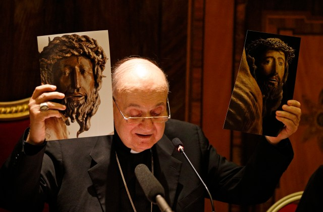 Cardinal Angelo Comastri, archpriest of St. Peter's Basilica, holds before and after restoration photos of a wooden crucifix from the 14th century during a media opportunity in St. Peter's Basilica at the Vatican Oct. 28. (CNS/Paul Haring)