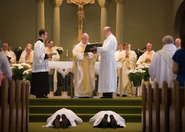 David Parker, left, and his son David Jr., lay prostrate during an ordination Mass at Assumption of the Blessed Virgin Mary Church in Pulaski, Wis., May 7. The elder Parker was ordained a permanent deacon and his son was ordained a transitional deacon as part of his formation for the priesthood. (CNS/Sam Lucero, The Compass)