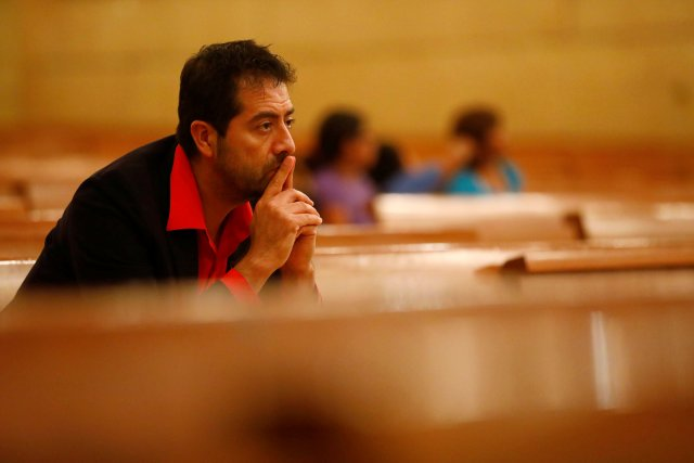Ernesto Vega of the Archdiocese of Los Angeles Hispanic ministry, listens as Archbishop Jose H. Gomez leads an interfaith prayer service for the immigrant community Nov. 10 at the Cathedral of Our Lady of the Angels in Los Angeles. (CNS/Reuters)