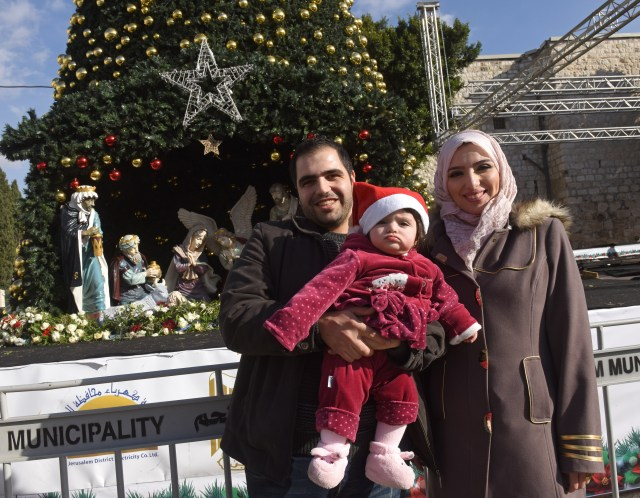 Muslim Palestinian Ashraf Natsheh, 28, holds his daughter Lara, 10 months, next to his wife, Shahad, 26, in front of the Christmas tree in Manger Square Dec. 5 in Bethlehem, West Bank. They had been unable to get into Bethlehem last year. (CNS/Debbie Hill)