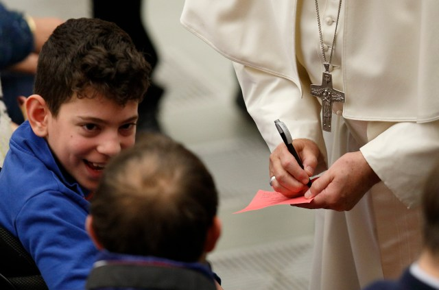 A boy smiles as Pope Francis signs an autograph for him during the pope's general audience in Paul VI hall at the Vatican Dec. 7. (CNS/Paul Haring)