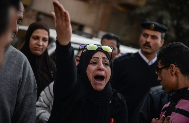 A woman reacts outside the Coptic Orthodox cathedral complex Dec. 11 after an explosion inside the complex in Cairo. (CNS/EPA)