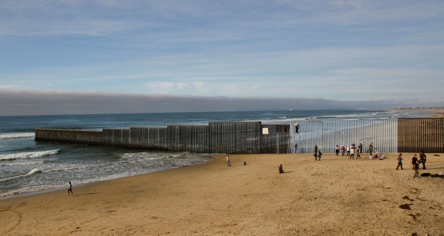 People in Tijuana, Mexico, stand next to a wall separating Mexico and the United States Dec. 10. (CNS photo/Jorge Duenes, Reuters)