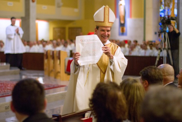 Bishop Michael F. Burbidge displays the apostolic letter from Pope Francis appointing him as the fourth bishop of the Arlington Diocese during his installation Mass Dec. 6 at the Cathedral of St. Thomas More in Arlington. (CNS photo/Ashleigh Buyers, Catholic Herald)