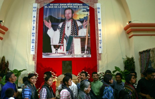 CATHOLICS WALK PAST PICTURE OF FATHER ROTHER AT GUATEMALAN CHURCH