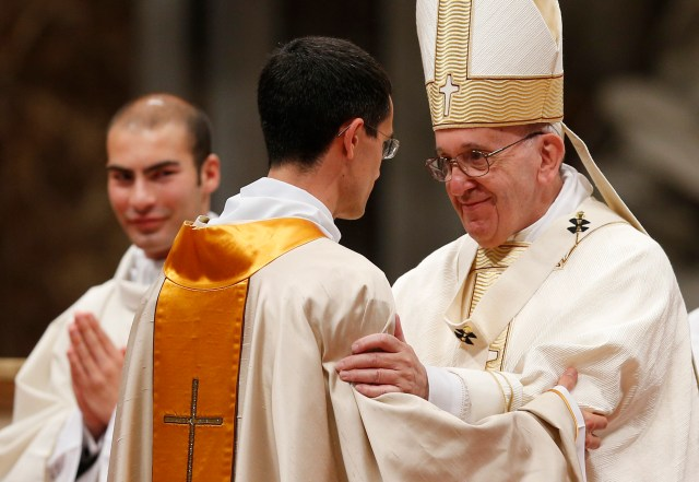 Pope Francis greets a new priest during the ordination Mass of 11 priests in St. Peter's Basilica at the Vatican last April. (CNS/Paul Haring)