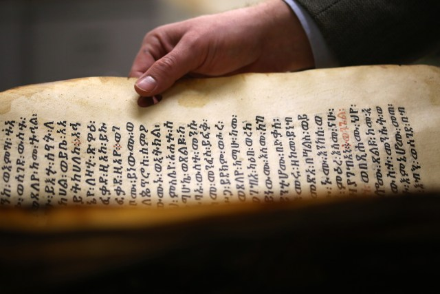 Aaron M. Butts, assistant professor of Semitic languages and literature at The Catholic University of America in Washington holds a possible 16th-century Ethiopic liturgical manuscript. The university is the holder of the fifth largest collection of Ethiopian Christian manuscripts in the United States and the largest collection of Ethiopian Islamic manuscripts outside Ethiopia. (CNS/Tyler Orsburn)