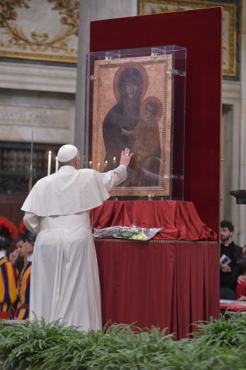 """Pope Francis touches the Marian icon, """"Salus Populi Romani,"""" (health of the Roman people), during an evening prayer vigil with young people at the Basilica of St. Mary Major in Rome April 8. (CNS/L'Osservatore Romano)"""