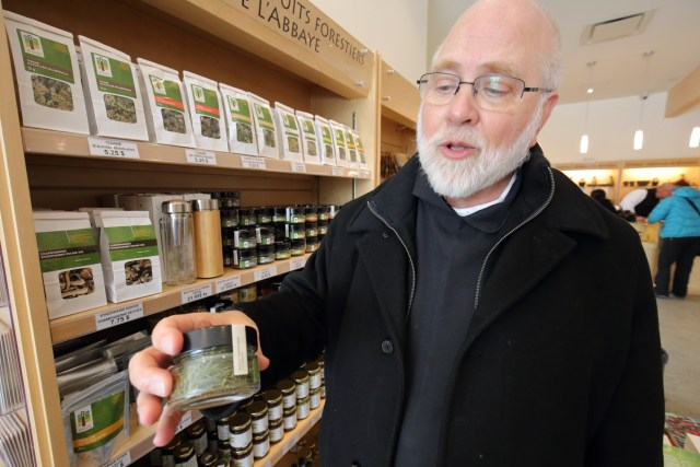Abbot Andre Barbeau of Val Notre-Dame Cistercian abbey in Saint-Jean-de-Matha, Quebec, holds a jar of larch needles, used in salads and soups produced at the abbey and sold in its gift shop. (CNS/Philippe Vaillancourt, Presence)