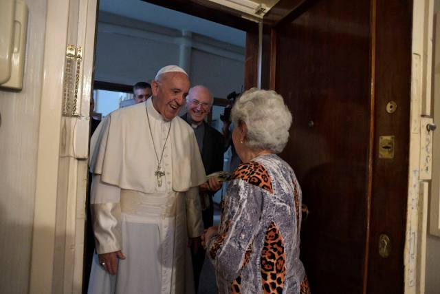 Pope Francis greets a resident as he arrives to give an Easter blessing to a home in a public housing complex in Ostia, a Rome suburb on the Mediterranean Sea, May 19. (CNS/L'Osservatore Romano)